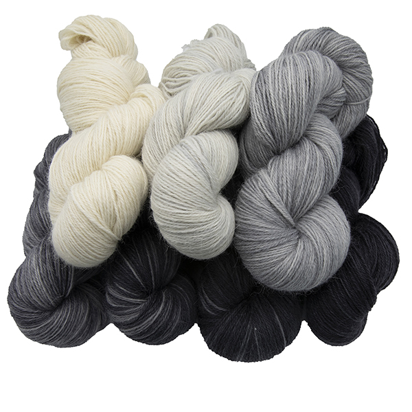 Skeins of hand dyed britsock yarn - cream, greays and balck