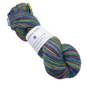 Skein of hand dyed yarn in emerald rainbow