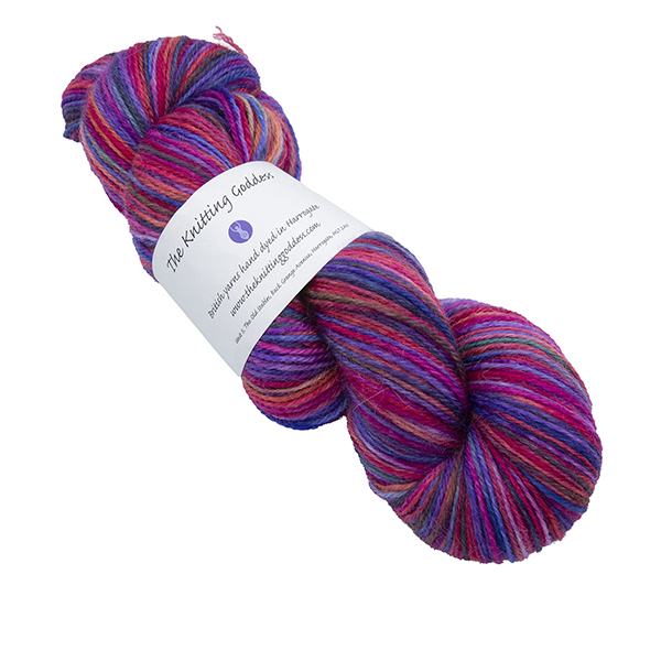 Skein of hand dyed yarn in pink rainbow