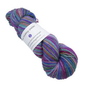 Skein of hand dyed yarn in purple rainbow