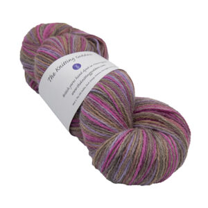 skein of chcolate box colour hand dyed Britsock yarn with browns, pink and purple from The Knitting Goddess with ball band