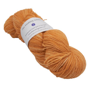 skein of marmalade orange colour hand dyed Britsock yarn from The Knitting Goddess with ball band
