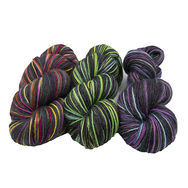 three skeins of hand dyed yarn in black with turquoise and yellow, black with pink and yellow, black with pink and turquoise solid colours, arranged in a row