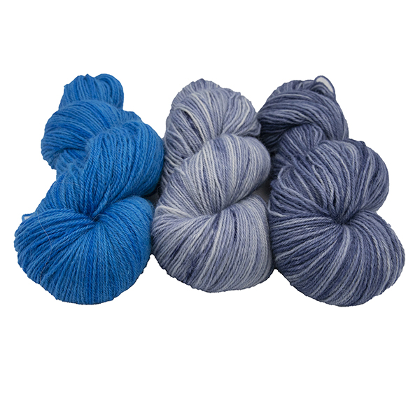 three skeins of hand dyed yarn in slate, electric blue and dark slate semi solid colours, arranged in a row