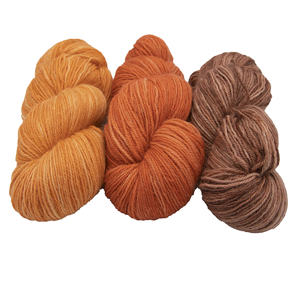 three skeins of hand dyed yarn in marmalade orange, copper and toffee semi solid colours, arranged in a row