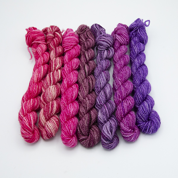 seven mini skeins of yarn in assorted shades of pink