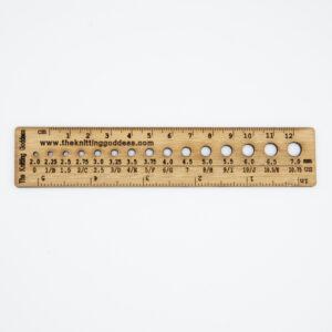 bamboo wood ruler with needle gauge holes on white background