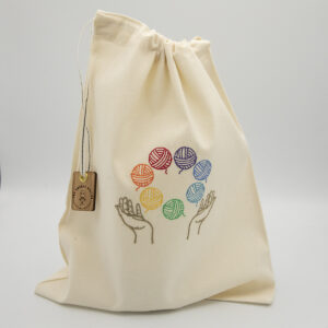 embroidered cream cotton drawstring bag. Embroidery is of two hands juggling 7 balls of yarn, one in each colour of the rainbow. The lad closes with a cream and white ribbon and is finished with a wooden tag bearing The Unruly Stitch logo