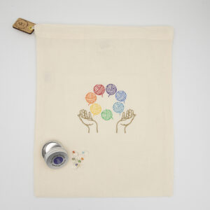 embroidered cream cotton drawstring bag. Embroidery is of two hands juggling 7 balls of yarn, one in each colour of the rainbow. The lad closes with a cream and white ribbon and is finished with a wooden tag bearing The Unruly Stitch logo. Sitting on the bag is a small round tin with The Knitting Goddess logo and eight jump ring stitch markers made with assorted beads
