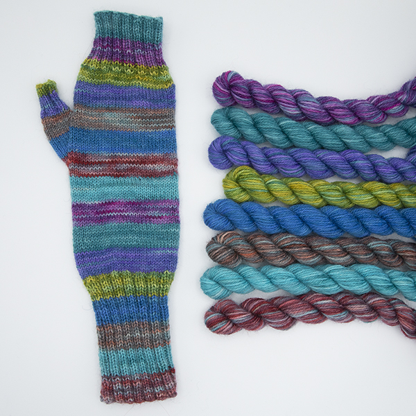 fingerless mitt knitted winarrow stripes of colour shown with mini skeins beside it.