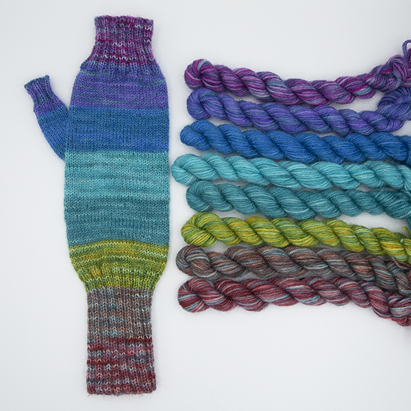 fingerless mitt knitted with wide stripes of colour shown with mini skeins beside it.
