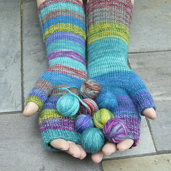 hands wearing striped fingerless mitts and holding small balls of yarn