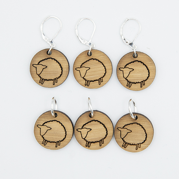 bamboo disc stitch markers engraved with sheep. set of six. white background.