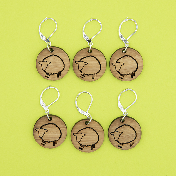 bamboo disc stitch markers engraved with sheep. lever back catch fittings. shown with pone open and one closed. black background.