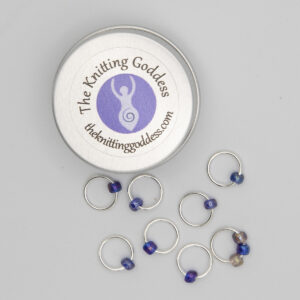 set of eight stitch markers made with jump rings and blue and purple beads. Shown with a small round storage tin with The Knitting Goddess logo