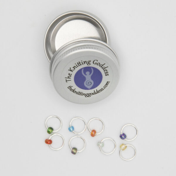 set of eight stitch markers made with jump rings and small beads in different colours. Shown with a small round storage tin with The Knitting Goddess logo