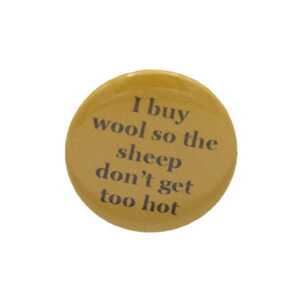 Yellow button badge with black writing which reads I buy wool so the sheep don't get too hot