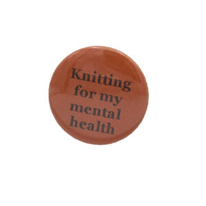 Orange button badge with black writing which reads Knitting for my mental health