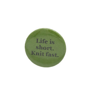 Green button badge with black writing which reads Life is short. Knit fast.