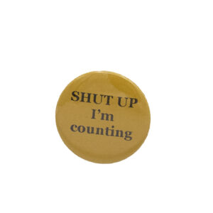 Yellow button badge with black writing which reads SHUT UP I'm counting