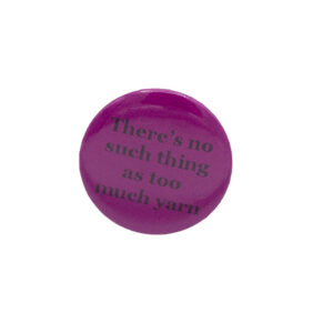 Pink button badge with black writing which reads There's no such thing as too much yarn