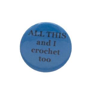 Turquoise button badge with black writing which reads ALL THIS and I crochet too