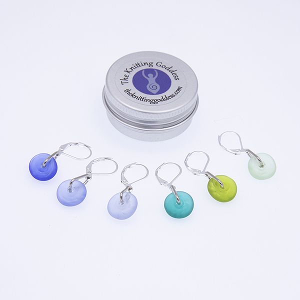 six blue and green glass stitch markers with a round storage tin