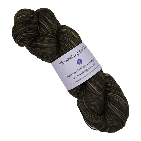 skein of darkest gold hand dyed yarn with The Knitting Goddess label