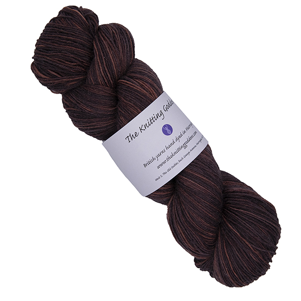 skein of darkest orange hand dyed yarn with The Knitting Goddess label
