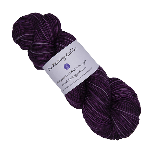 skein of darkest raspberry hand dyed yarn with The Knitting Goddess label