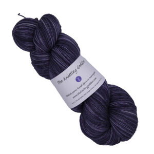 skein of darkest violet hand dyed yarn with The Knitting Goddess label