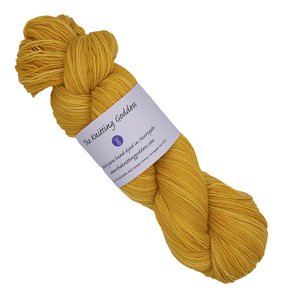 skein of gold hand dyed yarn with The Knitting Goddess label