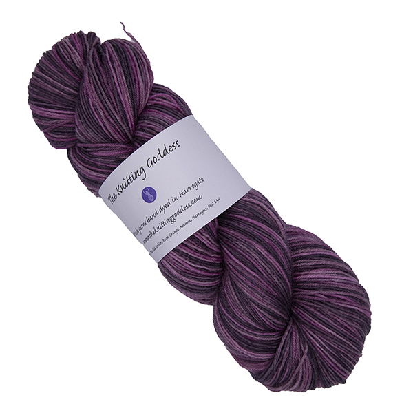 skein of heathers hand dyed yarn in plums and greys with The Knitting Goddess label