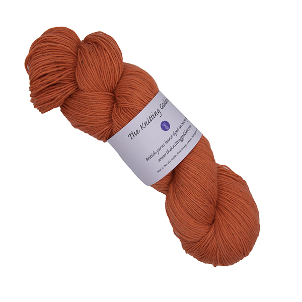 skein of orange hand dyed yarn with The Knitting Goddess label