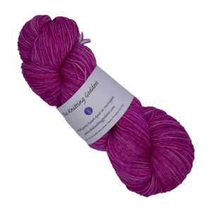 skein of raspberry hand dyed yarn with The Knitting Goddess label