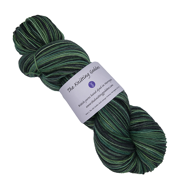 skein of hand dyed yarn in the moors colourway which is greens and greys with The Knitting Goddess label
